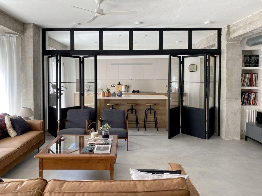 Salón abierto a la cocina con puertas plegables y suelo continuo de microcemento