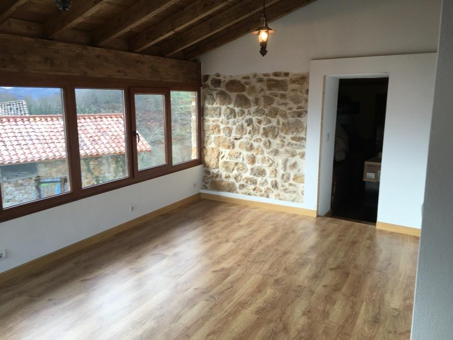 Salón acabado en piedra, madera y pintura.