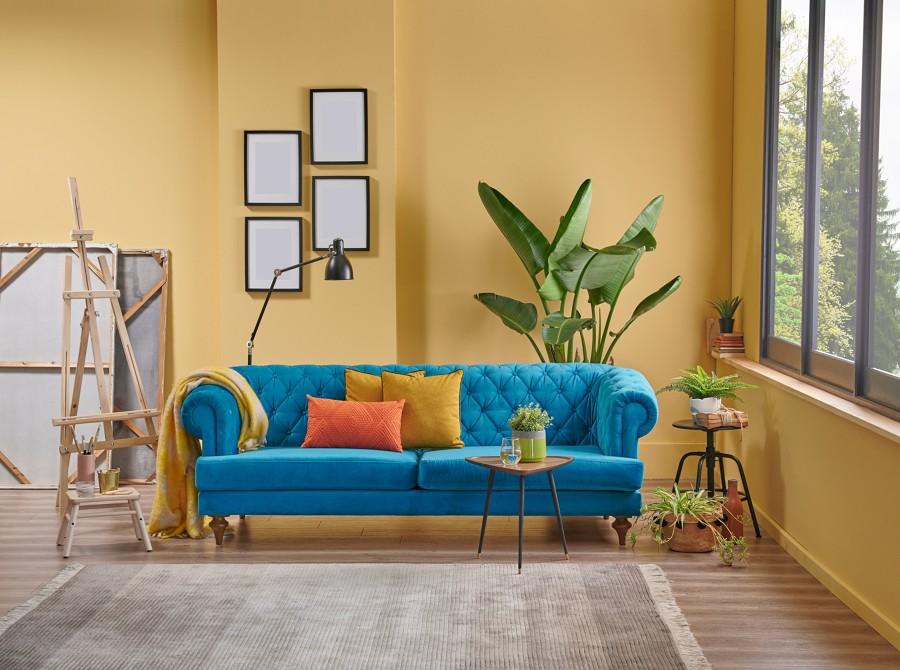 Salón amarillo con sofá chester en azul