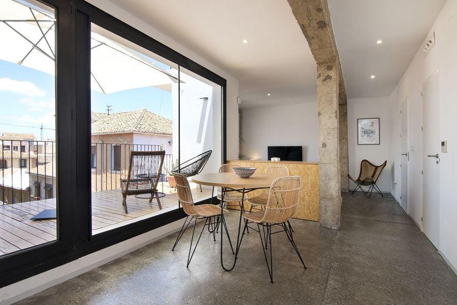 Salón comedor con gran ventanal de acceso a terraza sin persiana