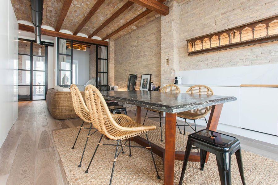 Salón comedor con muros de ladrillo originales y puertas de vidrio y metal