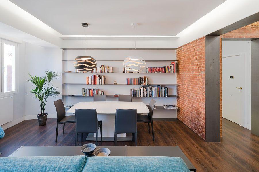 Salón comedor con paredes de ladrillo visto y estanterías voladas.