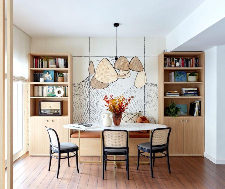 Salón con librerías de madera y banco de mesa a medida