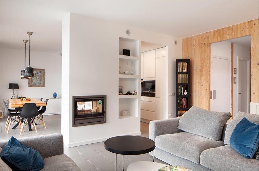 Salón con pared de pladur que integra librería y estufa