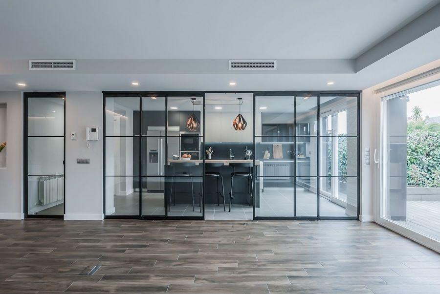 Salón con puertas acristaladas que dan a la cocina