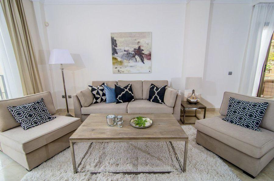 Salón con sofá tapizado y alfombras de pelo largo