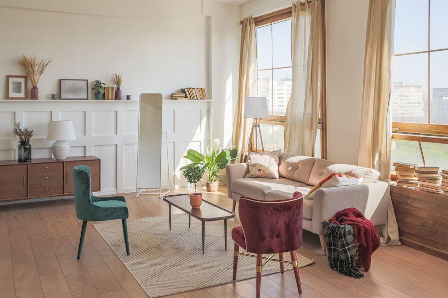 Salón con ventanas de madera y cuarterones de escayola en la pared