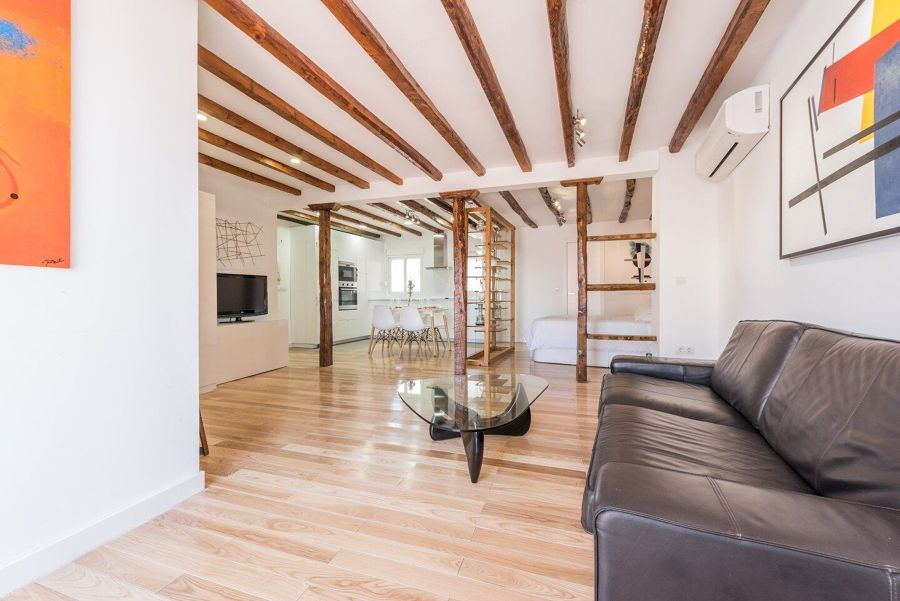 Salón con vigas en el techo y pilares de madera
