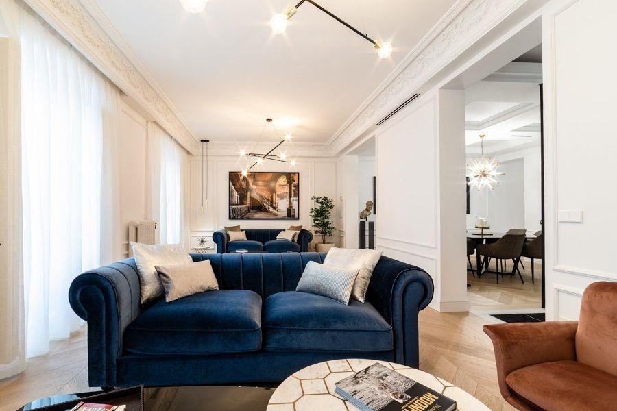Salón de estilo clásico y romántico con molduras y sofás tapizados