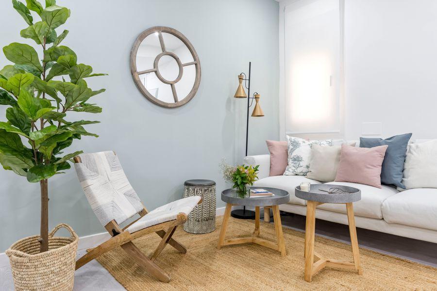 Salón de estilo nórdico con butaca de madera