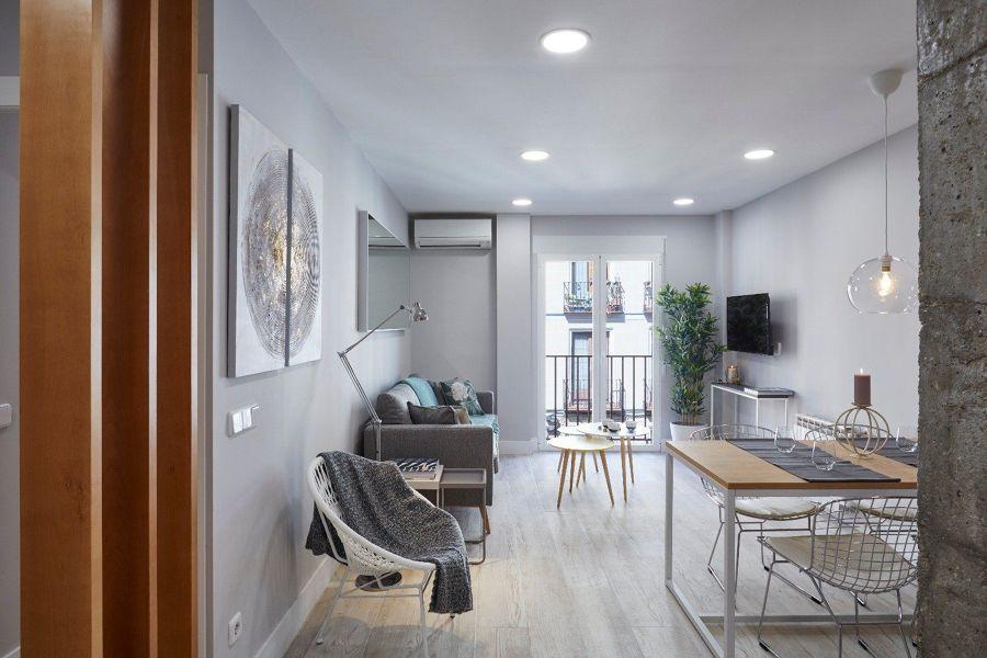 Salón de estilo nórdico con suelos claros y paredes grises