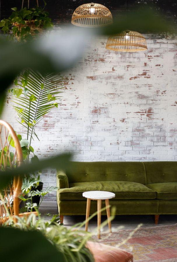 Salón de estilo tropical con sofá verde