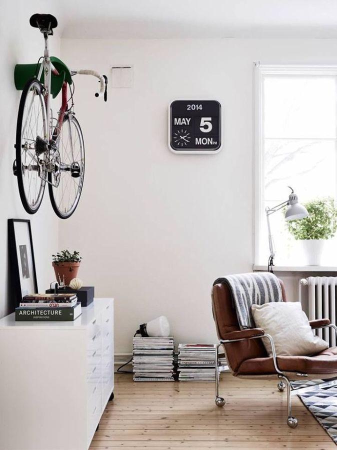 Salón estilo nórdico con bicicleta en pared