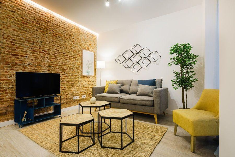 Salón nórdico y rústico con pared de ladrillo