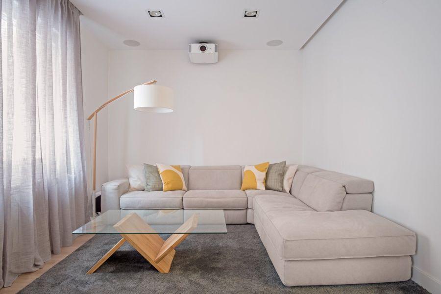 Salón pequeño con sofá en esquina y proyector.