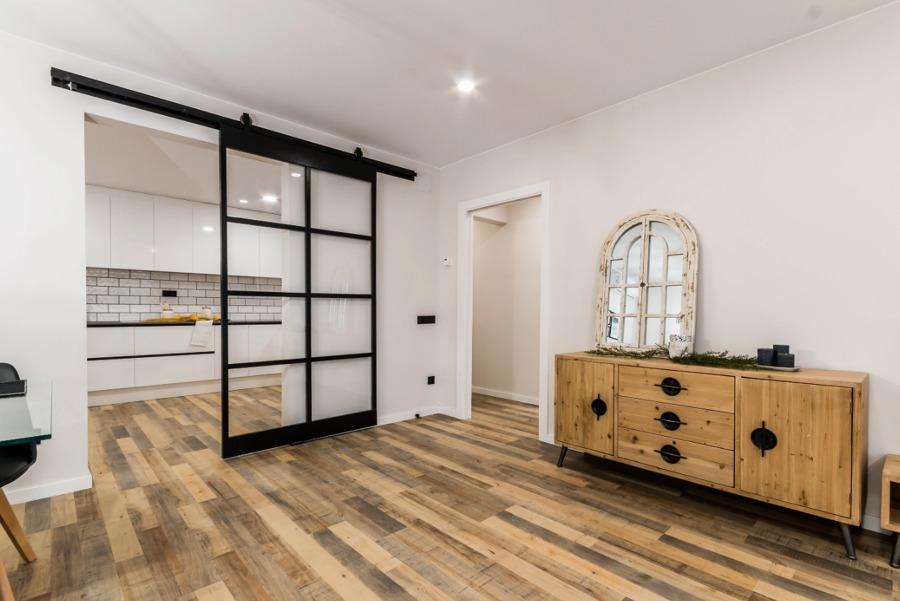 Salón sin puerta de entrada (solo marco) y corredera de hierro y metal en la cocina