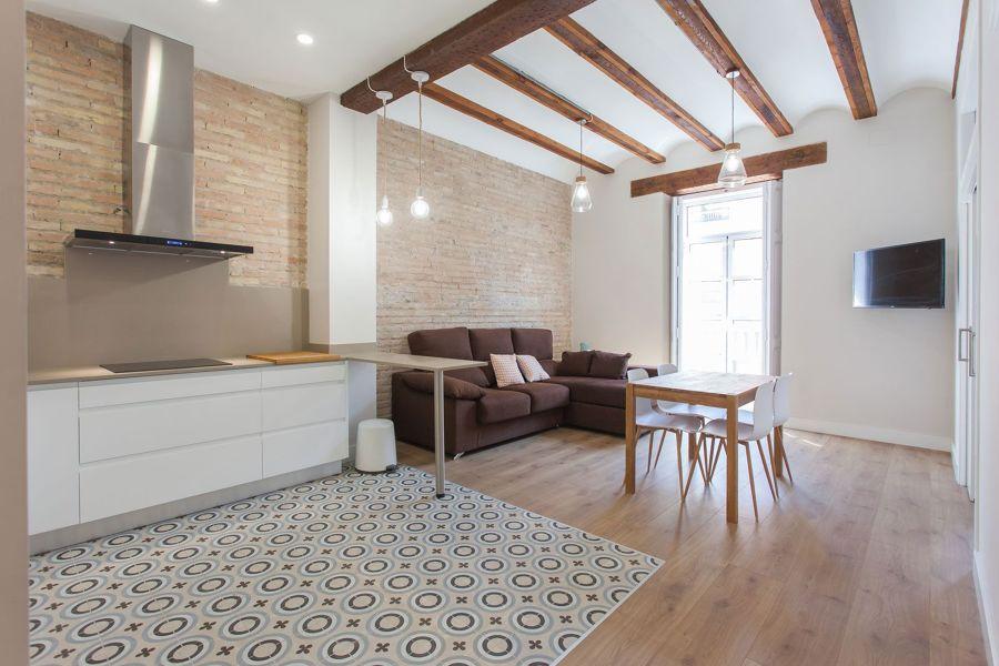 Salón y cocina de planta abierta con techo alto