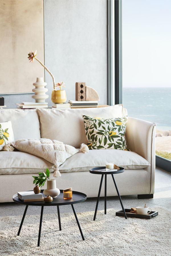 Sofá blanco con cojines de tonos naturales.