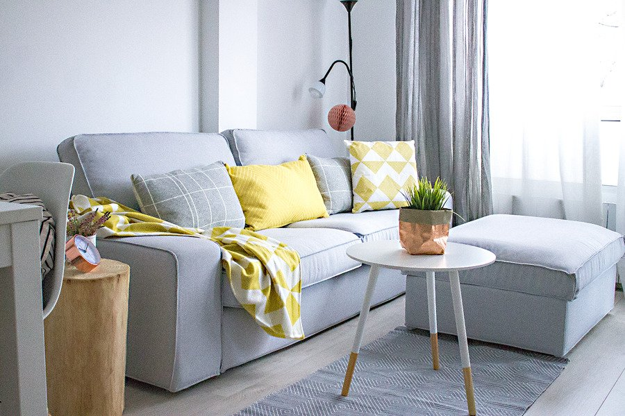 Sofá en gris y cojines en amarillo