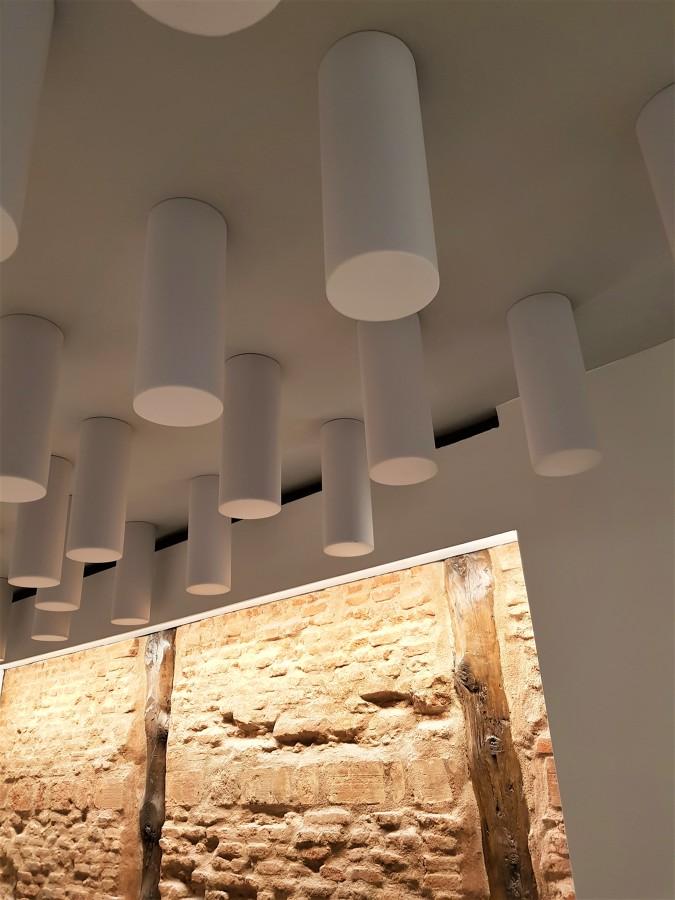 Techo con cilindros aislantes acústicos y pared de ladrillo vista