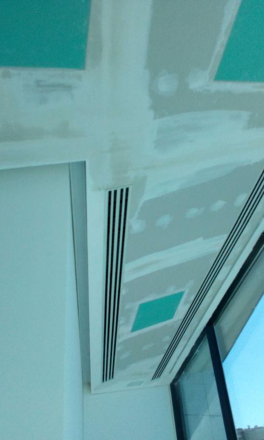 Techo inclinado con sistema de climatizacion de rejillas lineales