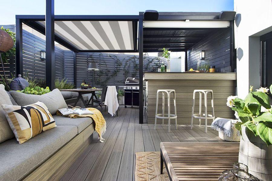 Terraza con gran sofá de obra, pérgola y cocina exterior