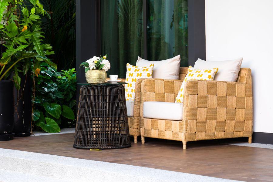 Terraza con mobiliario de mimbre y cojines de flores