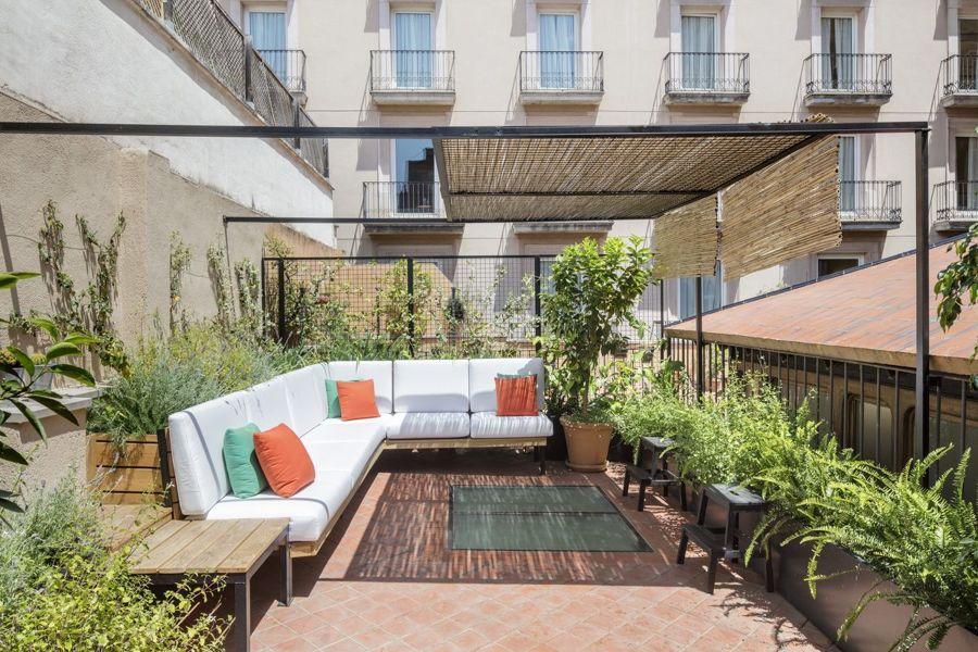 Terraza mediterránea con mobiliario de madera fijo.