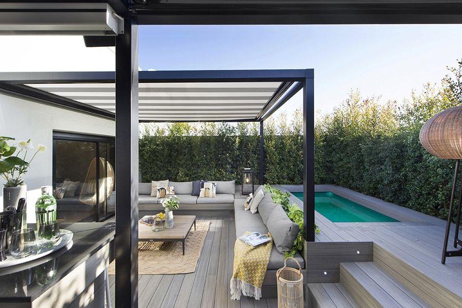 Terraza moderna con gran sofá de obra, pérgola y piscina