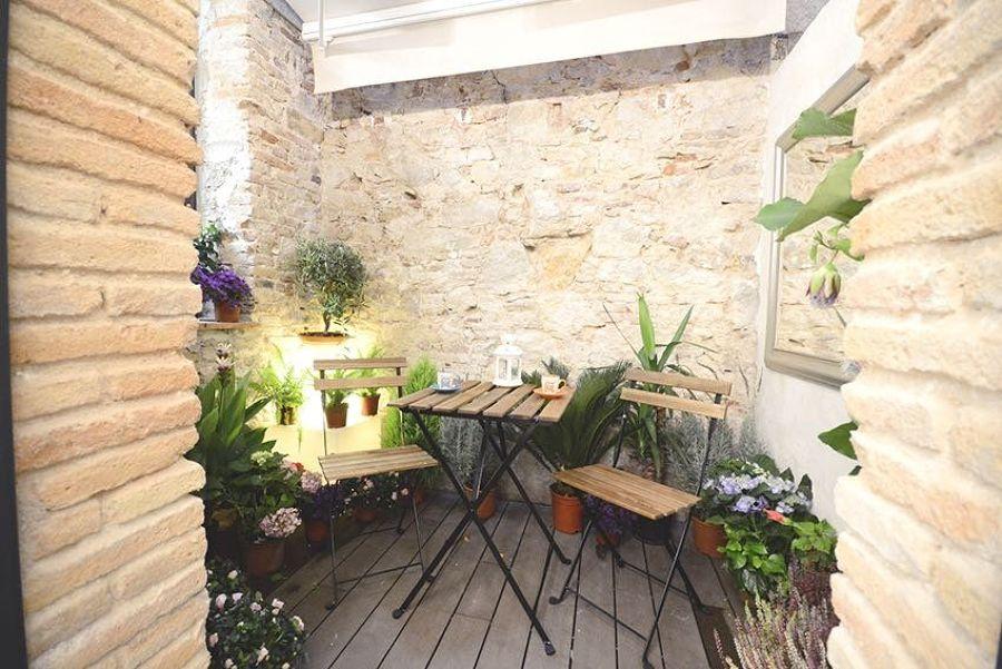Terraza pequeña con paredes de piedra