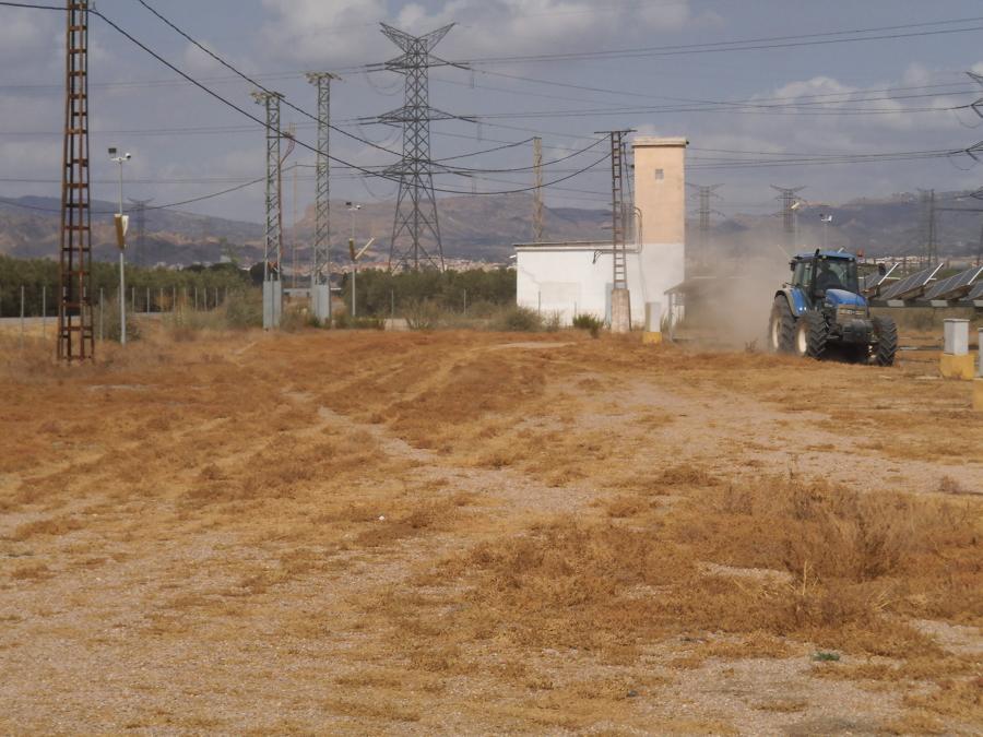tractor con desbrozadora de cadenas suspendida en pleno trabajo