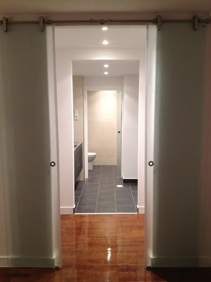 Vestidor abierto al baño principal con puertas de cristal