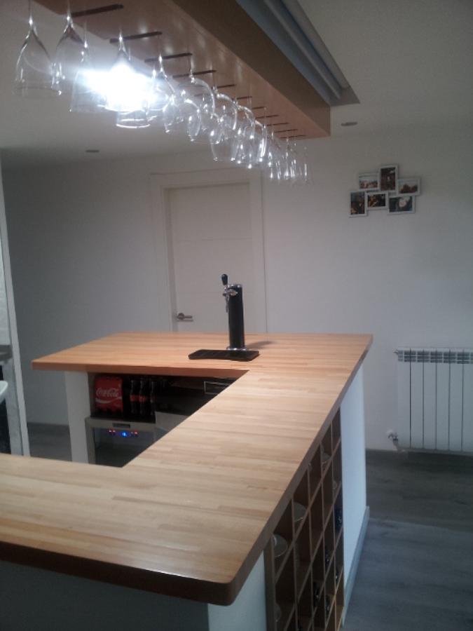 Vista barra con tirador, proyector en techo, copas colgadas y botellero