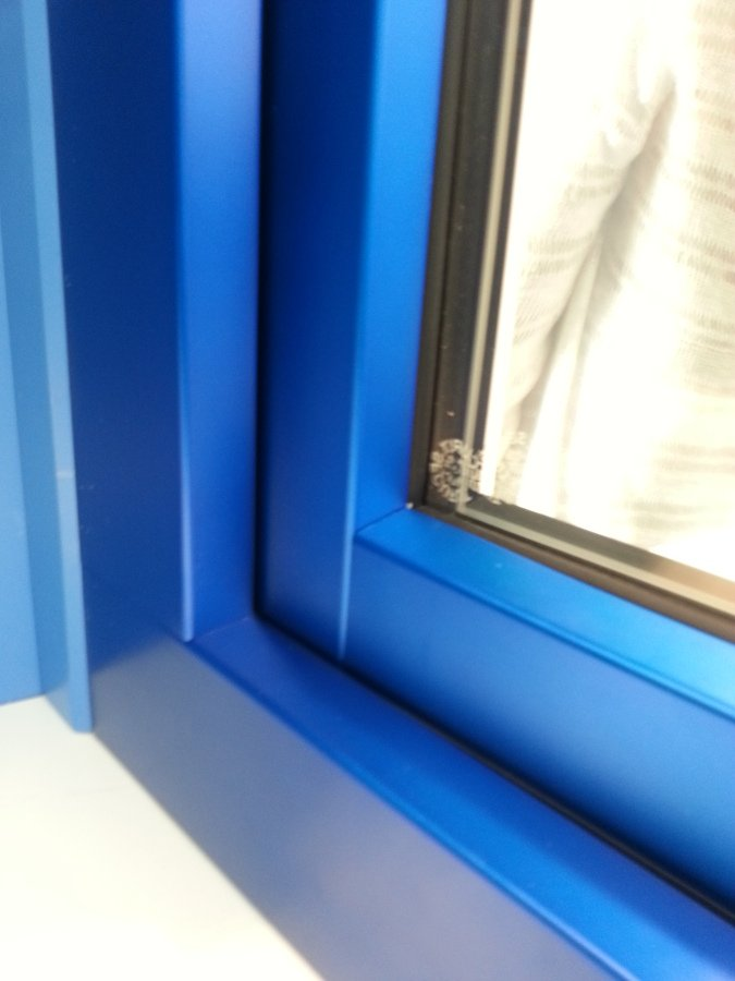 Vista exterior de una ventana azul con aluclip