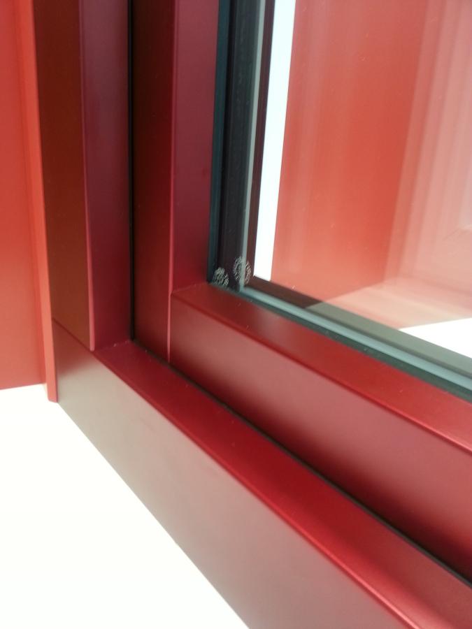 Vista exterior de una ventana roja con aluclip