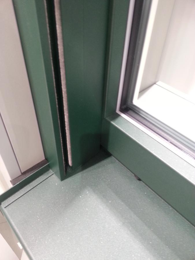 Vista exterior de una ventana verde  con aluclip