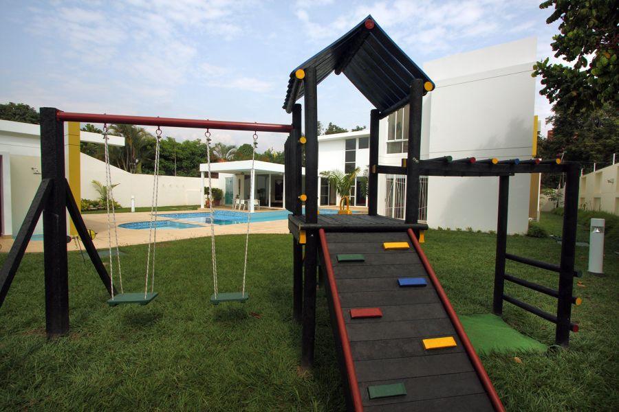 Zona de juegos infantil con columpios en jardín
