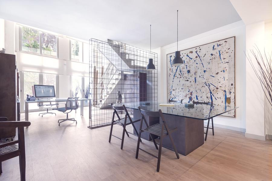 Zona de reuniones abierta con mesa de cristal y separación conceptual