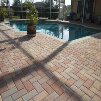 Adoquín tricolor en rededor de piscina en espiga