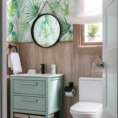 baño con friso de madera y papel pintado con motivos tropicales