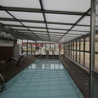 Cerramiento de piscina con techo móvil y ventanas abatibles