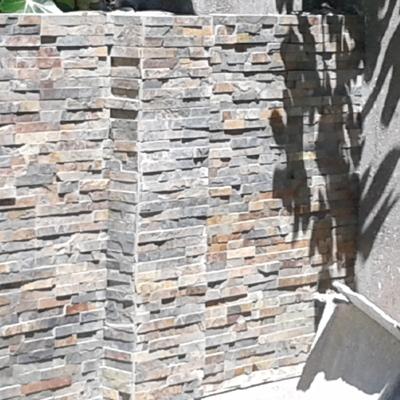 Colocación de piedra natural sobre un muro de ladrillo en un  patio de León