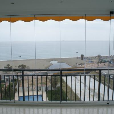 Cortina de cristal con puerta de paso para cerrar salón y terraza