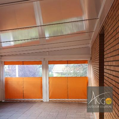 Cerramiento con techo fijo de panel sándwich y toldos verticales perimetrales