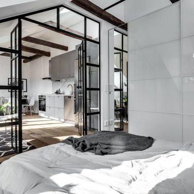 Dormitorio con pared de vidrio y carpintería metálica