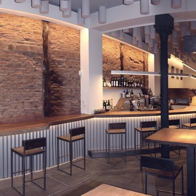 Entrada del restaurante con barra de madera continua e iluminación ambiental
