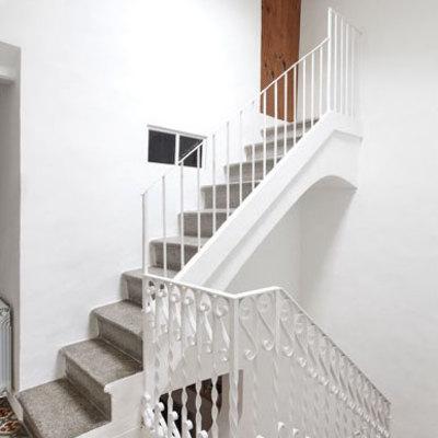 Escalera de peldaños de piedra y rejería
