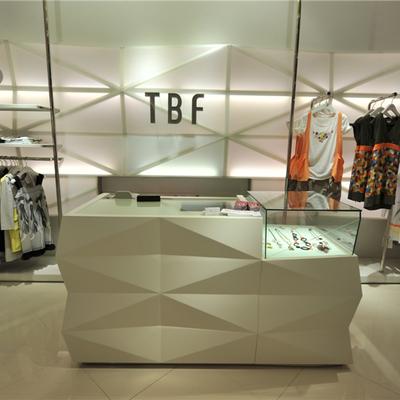 Diseño para tienda de moda con mesa expositiva y soporte de ropa, en Barcelona