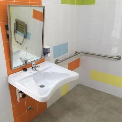 Lavabo para discapacitados con espejo y dispensador de jabón. Barra de sujeción en L.