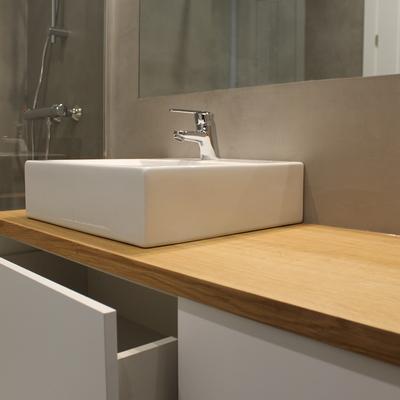 Un baño con microcemento y encimera de roble